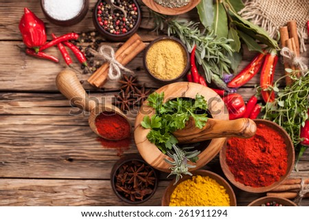 Various kind of spices on wooden table, shot from aerial view - stock photo