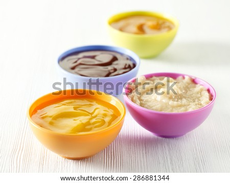 various kinds of baby food in plastic bowls - stock photo