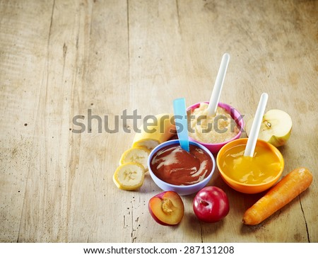 various kinds of baby food in plastic bowls, top view - stock photo
