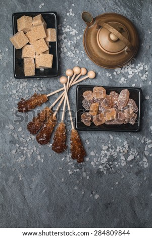 Various kinds of brown sugar on black background, top view - stock photo