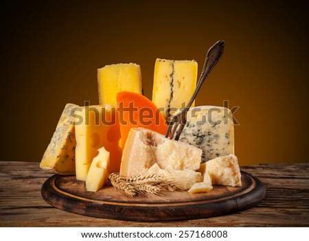 Various kinds of cheese served on wooden table - stock photo