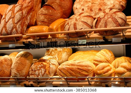Various kinds of fresh baked artisan bread on the shelves in the bakeshop. - stock photo