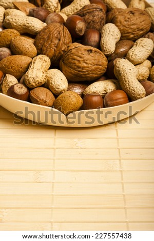 various kinds of nuts - dried fruit - over wooden background - stock photo