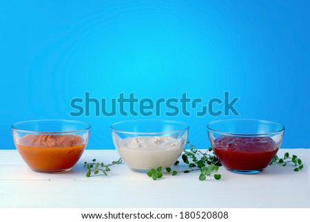 Various kinds of sauces on blue background side view. - stock photo