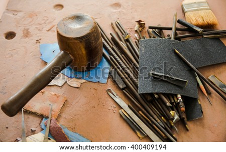 Various kinds of Sculpting Tools laying down on dirty wooden table - stock photo