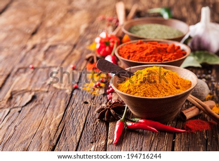 Various kinds of spices on wooden planks - stock photo