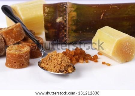 Various kinds of sugar, brown sugar, reed sugar, sugar cane and cane. - stock photo