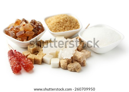 Various kinds of sugar in bowls isolated on white - stock photo
