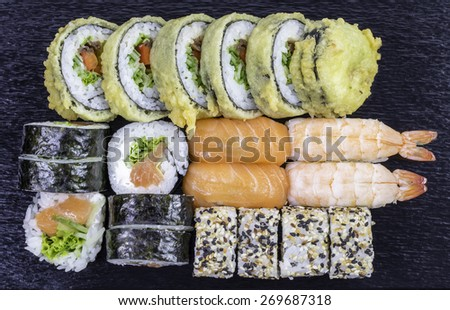 Various kinds of sushi food on black stone - stock photo