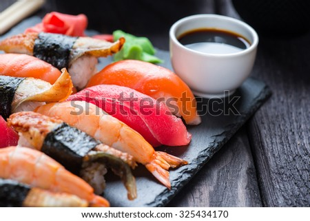 Various kinds of sushi served on black stone - stock photo