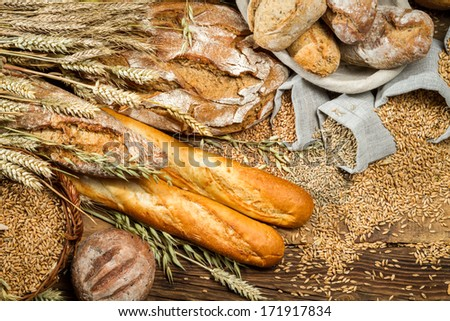 Various kinds of whole wheat bread on old wooden table - stock photo