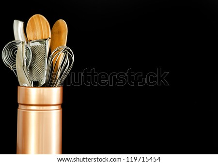 Various kitchen tools in a ceramic container on a black background - stock photo