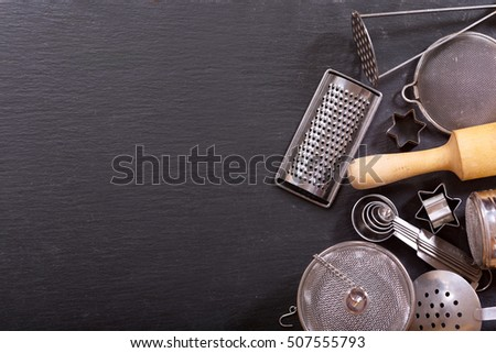 Various kitchen utensils on dark background, top view