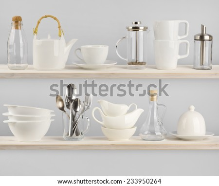 Various kitchen utensils on wooden shelves - stock photo