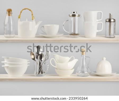 Various kitchen utensils on wooden shelves - stock photo