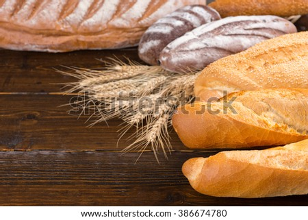 Various leavened whole wheat and sourdough white bread loaves with wheat stalks on table
