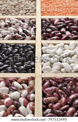 Various legume grains close-up in wooden box: white, black and purple speckled beans, red and green lentils. Shallow DOF.