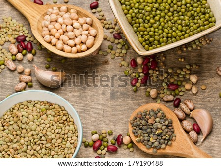 Various legumes in wooden spoon and bowl on old wooden background - stock photo