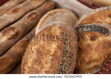 Various loaves of home made bread on display at a market.