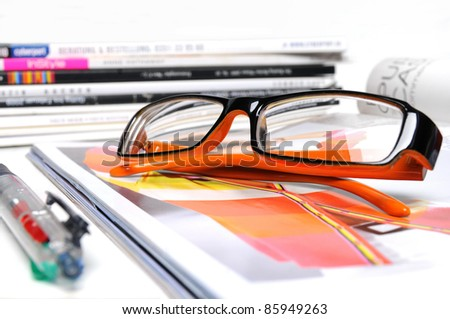 Various magazines with orange colored glasses and ball pen on white background - stock photo