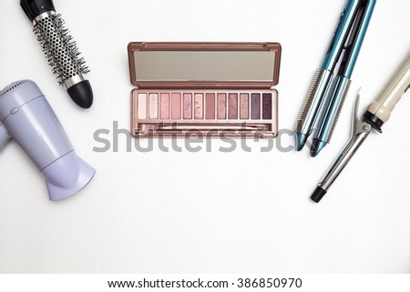 Various makeup products and hairdressing tools on white background with copyspace
