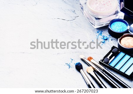 Various makeup products in blue tone with copyspace