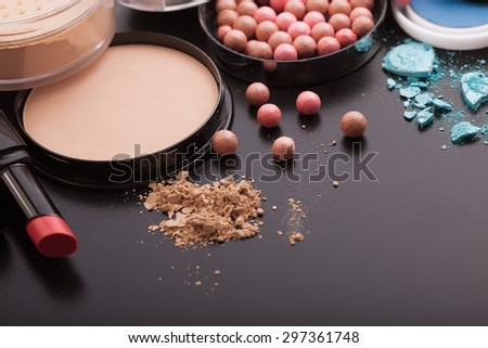 Various makeup products on black background with copyspace