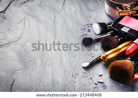 Various makeup products on dark background  - stock photo