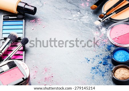 Various makeup products on dark background with copyspace - stock photo