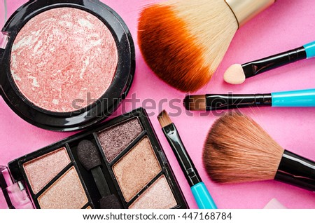 Various makeup products on pink background.