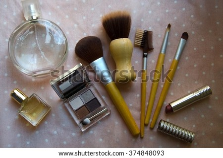 Various makeup products . Perfume, brush and cosmetic on a pink background. Top view.
