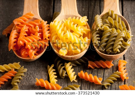 Various mix of pasta on wooden rustic background, sack and wooden spoons. Diet and food concept. Colored natural pasta. Spinach, beetroot, egg - stock photo