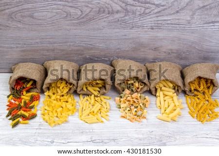 Various mix of pasta on wooden rustic background, sack. Diet and food concept. diversity - stock photo