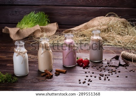 Various natural milkshakes on the background of hay and sackcloth. Beautiful interer. - stock photo