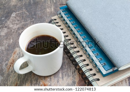 various note book with coffee cup on grunge wood