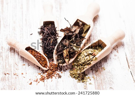 Various of dried tea in wooden scoops on white shabby table - stock photo