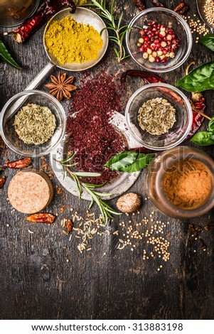 Various of spices and herbs on dark rustic wooden background, top view