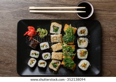 Various of sushi rolls with chopsticks on wooden table - stock photo