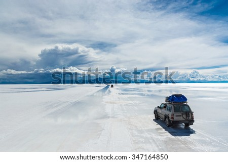 Various off-road vehicles driving onSalar de Uyuni - stock photo