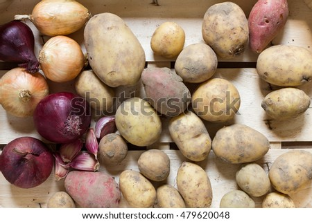 Various organic root vegetables such as potatoes, onions and garlic as a natural still life for healthy and vegetarian food as top view background image for summer, autumn and thanksgiving