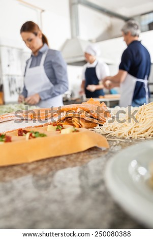 Various pastas on counter with chefs working in background at commercial kitchen - stock photo