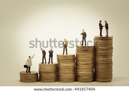 Various people standing on stacks of coins. - stock photo