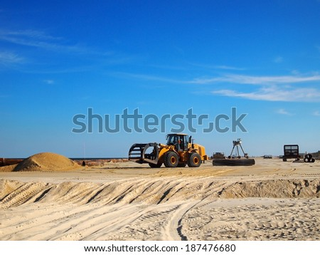 Various pieces of machinery and vehicles are scattered about on a portion of beach that is being replenished. - stock photo