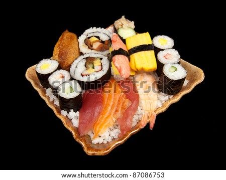Various pieces of sushi stacked on a plate on a pile of white rice isolated on black.