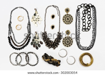 Various pieces of woman jewelry,black and gold,arranged against white board.Top view. - stock photo