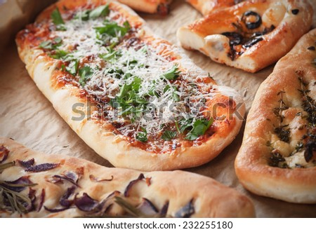 Various pizza and focaccia bread in baking tray - stock photo