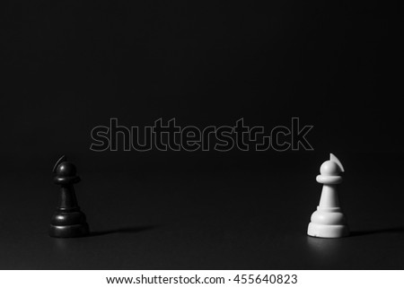 various plastic chess pieces stand on a black background