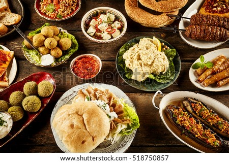 Various Plates Filled With Bread And Meat For Theme About Middle Eastern Food On Wooden Table