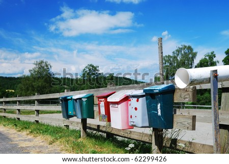 Various postboxes are hanging on the wood fence near the country road. - stock photo