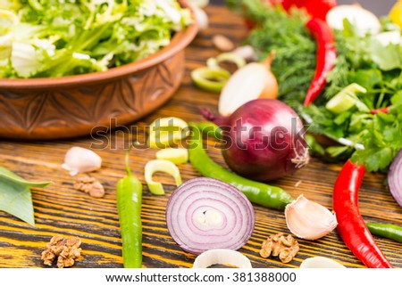 Various pungent vegetables and herbs such as pepper, onion and garlic with large bowl of salad in the background corner side
